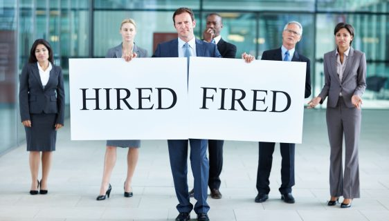 Business man with 'hired' and fired' board