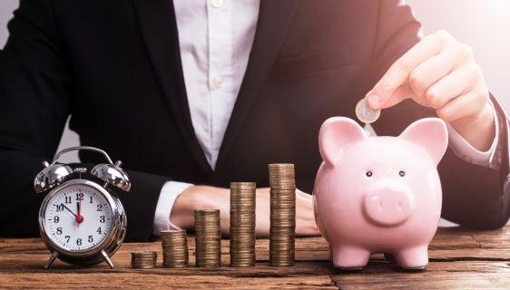 Businessperson's Hand Putting Coin In Piggybank