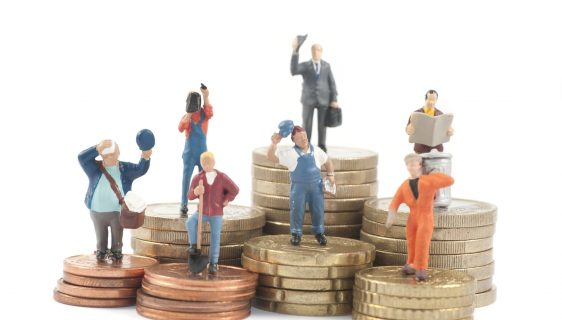 Miniature business people on stacks of coins